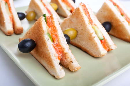 club tea sandwich with salmon and cucumbers on white bread photo