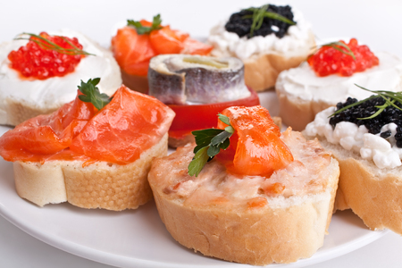 group of small sandwiches with red and black caviar, herring  and salmon photo