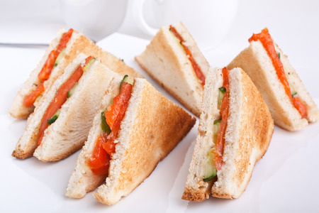 six salmon and cucumber club  sandwiches on white bread photo