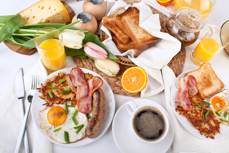 traditional large American breakfast of sunnyside up eggs, bacon, sasauge, hash browns, and toast 스톡 콘텐츠