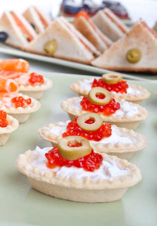 large group of canapes and sandwiches with caviar and fish photo