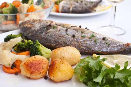 mediterranian: two servings of Sea Bream fish with vegetables and a glass of wine