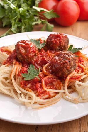 three meatballs with tomato sauce, spaghetti and parsley photo