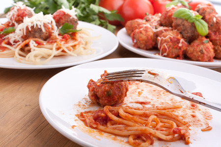 three servings of meatballs with tomato sauce, spaghetti and parsley photo
