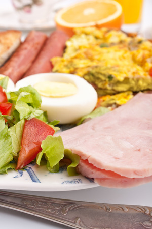 healthy breakfast with omelette, sausages, salad ad ham photo