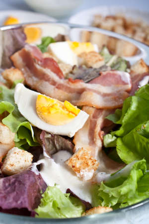 close up of caesar salad with bacon and eggs photo
