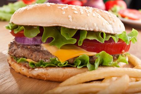 Cheeseburger und Pommes frites französisch auf einem Holztisch mit Zutaten Standard-Bild - 31593385