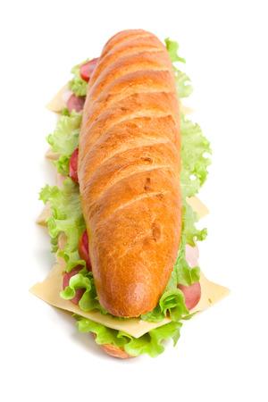 Lange Baguette-Sandwich mit Salat, Scheiben von frischen Tomaten, Schinken, Putenbrust und Käse Standard-Bild - 31593388