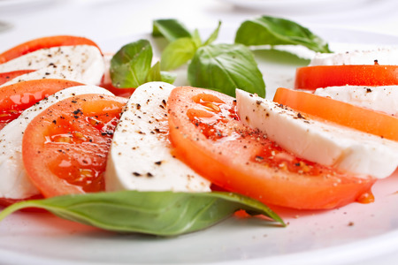 close up food: classic caprese salad - tomatoes, mozzarells and basil