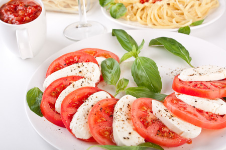 classic caprese salad and pasta with tomato sauce photo