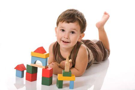 Een kleine jongen op de grond wordt gespeeld met blokken Stockfoto