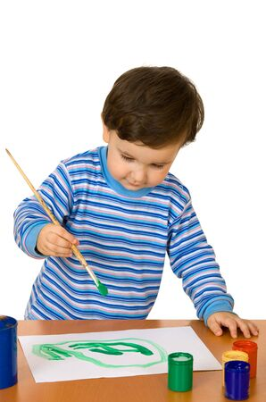 ni�os pintando: Ni�o pintando un cuadro con un pincel y acuarelas en una mesa