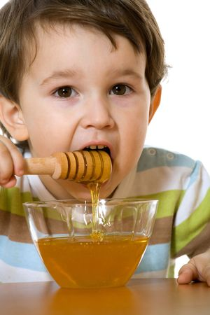 A little boy eats honey