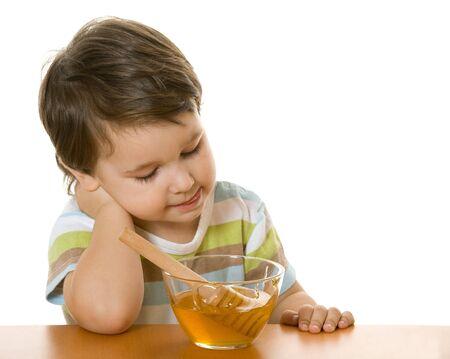 A boy licks lips looking on honey Stock Photo