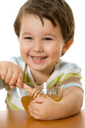 Een blij jongen houdt een kom met honing