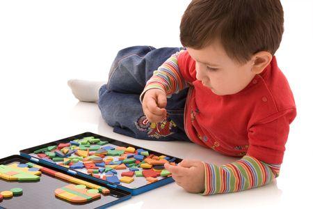 Het kind speelt met een magnetische puzzel
