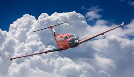 small red plane in the sky, in clouds