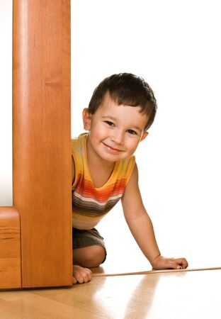 Little boy peeks out from a door photo