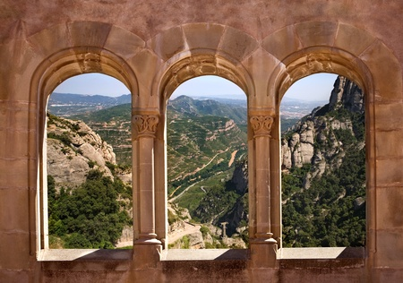 Kind from arch windows of a monastery of Monserrat on a valley Stock Photo