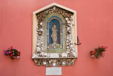 cockleshells: Icon of the Madonna with the baby decorated with sea cockleshells on the wall in an ancient fishing small village Camogli Stock Photo