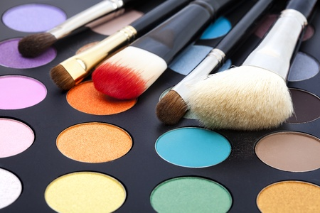 Set of make-up brushes on colorful eye shadows palette. Stock Photo