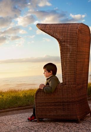 vacancier: Boy le vacancier dans un fauteuil au coucher du soleil