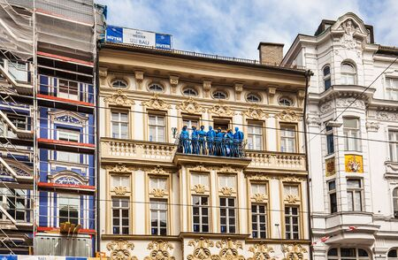 Innsbruck, Austria - May 6, 2017: Blue mannequins of builders standing on the balcony of the restored building in Innsbruck.