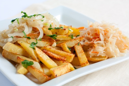 Sliced ​​potatoes with onions and sauerkraut on a white square plate photo