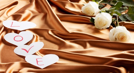 Beautiful white roses and a heart made of paper on a golden silk background  Holiday Cards photo