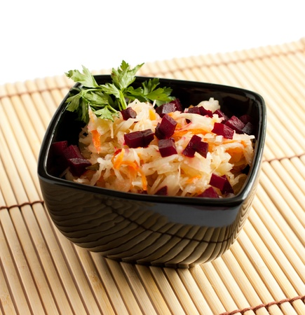 Crispy sauerkraut with diced beets and green parsley in black bowl     Isolated on white photo