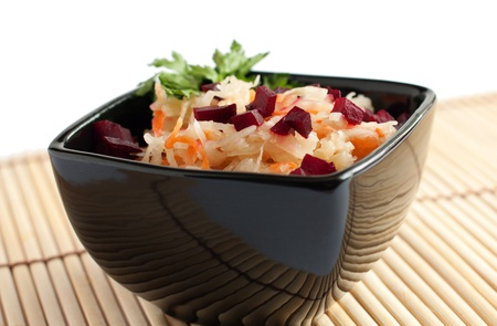 Salted cabbage  with  beet  and greens  in  the  square black bowl   Isolated on white photo