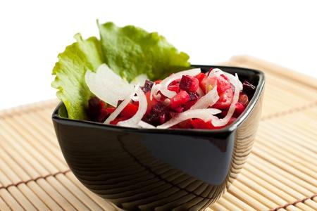 huzarensalade: Een voorproefje salade van gekookte groenten Russische salade in zwart kom geà ¯ soleerd op wit