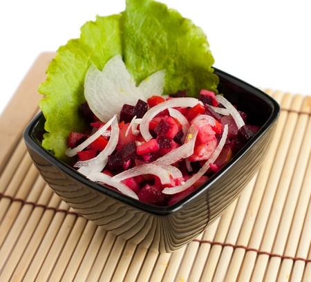 huzarensalade: Een Russische salade met semirings uien in zwart kom geà ¯ soleerd op wit