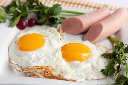 Traditional english breakfast food - fried eggs and sausages with greens Stock Photo
