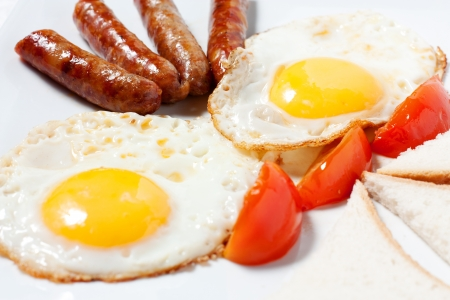 Fried eggs and fried sausage for breakfast. Stock Photo