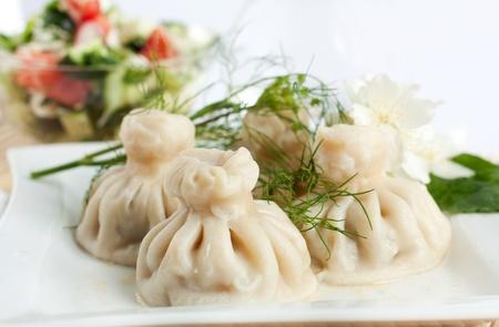 Georgian khinkali with salad on a white dish