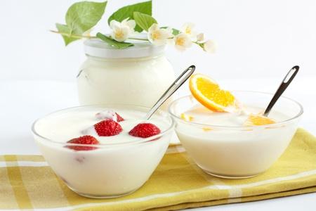 Orange and strawberry yogurt against the backdrop of a  jar of fresh yogurt