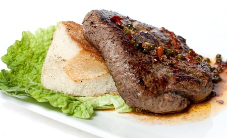 Large piece of roasted meat with sauce. White bread and green salad photo