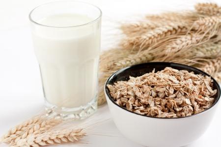 Vaso de leche y avena. Espigas de trigo en el fondo Foto de archivo