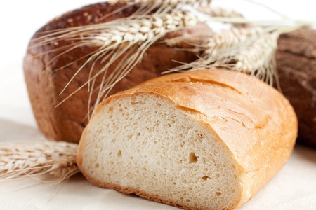 Different types of bread and wheat spikelets  Baton close up photo