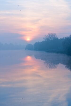 Cold autumn dawn. Fog on the river. Landscape photo