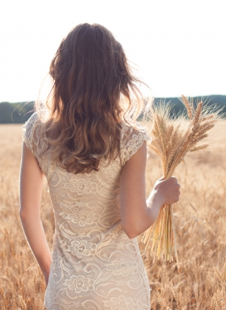 Girl's back in a wheat field with ears of wheat in the hands photo