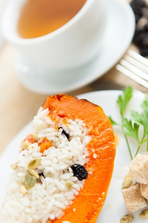Baked pumpkin with rice and raisins and cup of tea photo