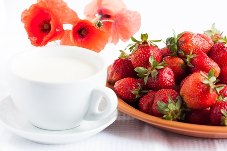 Cup of milk and juicy strawberries - a healthy breakfast Stock Photo