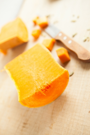 Half a pumpkin and a knife on a wooden surface, vertical photo