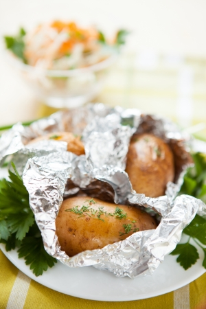 foil: Potatoes in foil not a white plate and a bowl of salad, close up