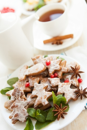 Cookies in the form of Christmas trees and a cup of tea, close up photo