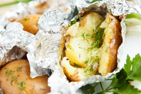 Baked potatoes with dill in foil, close up Stock Photo - 16394993