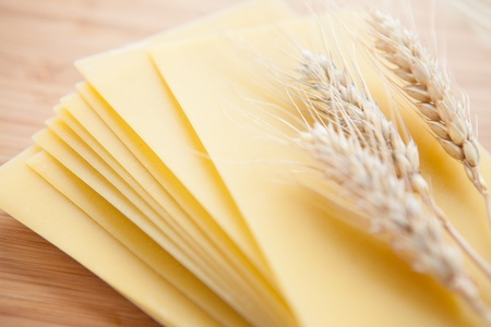 Pasta and wheat ears on a wooden surface, close up Stock Photo - 16756631