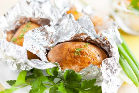 brown potatoes baked in foil, with greens Stock Photo - 17010107